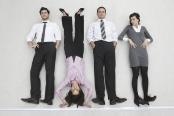 Four business people side byside, woman doing handstand, portrait, elevated view